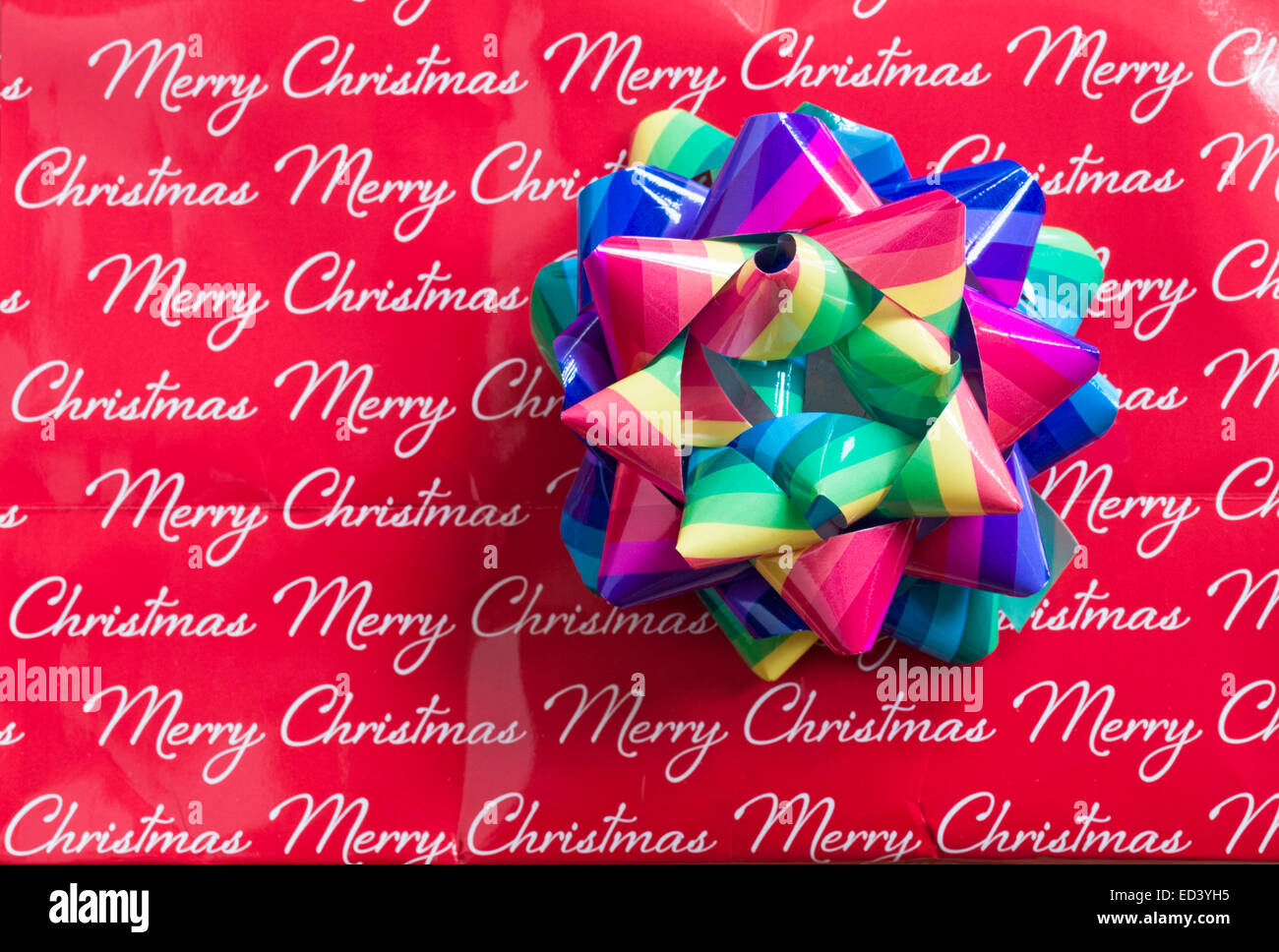 Colourful christmas gift bow stuck on merry christmas paper stock colourful christmas gift bow stuck on merry christmas paper negle Choice Image