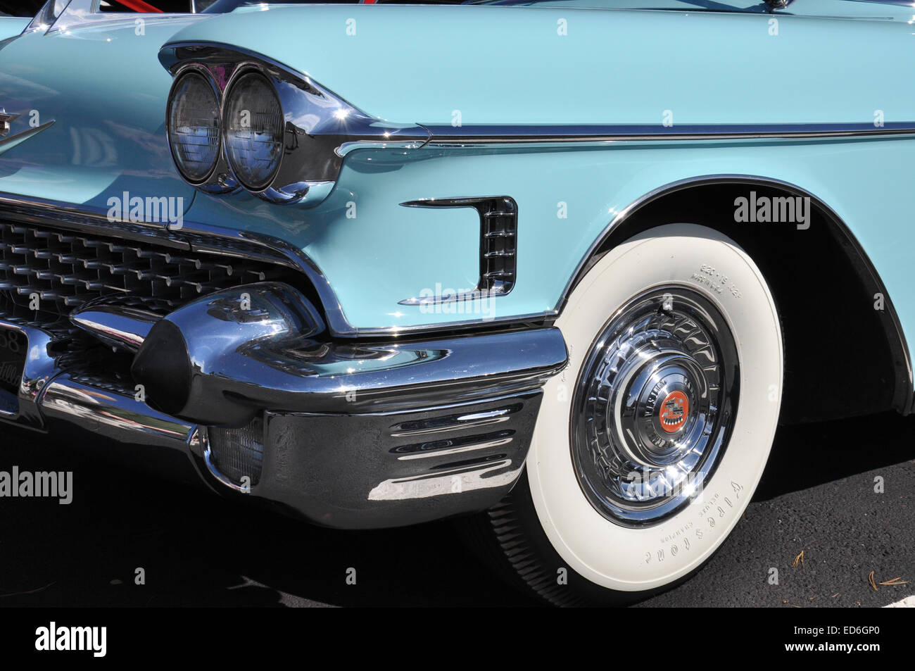 the front of a cadillac showing chrome and white wall tires stock image