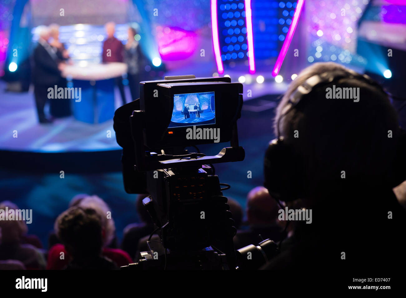 A video camera and cameraman recording a television tv broadcast ...