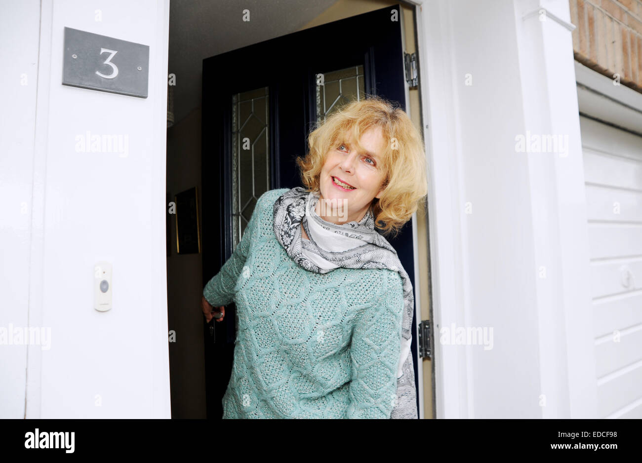 Stock Photo - Woman looking out of her front door to greet visitors
