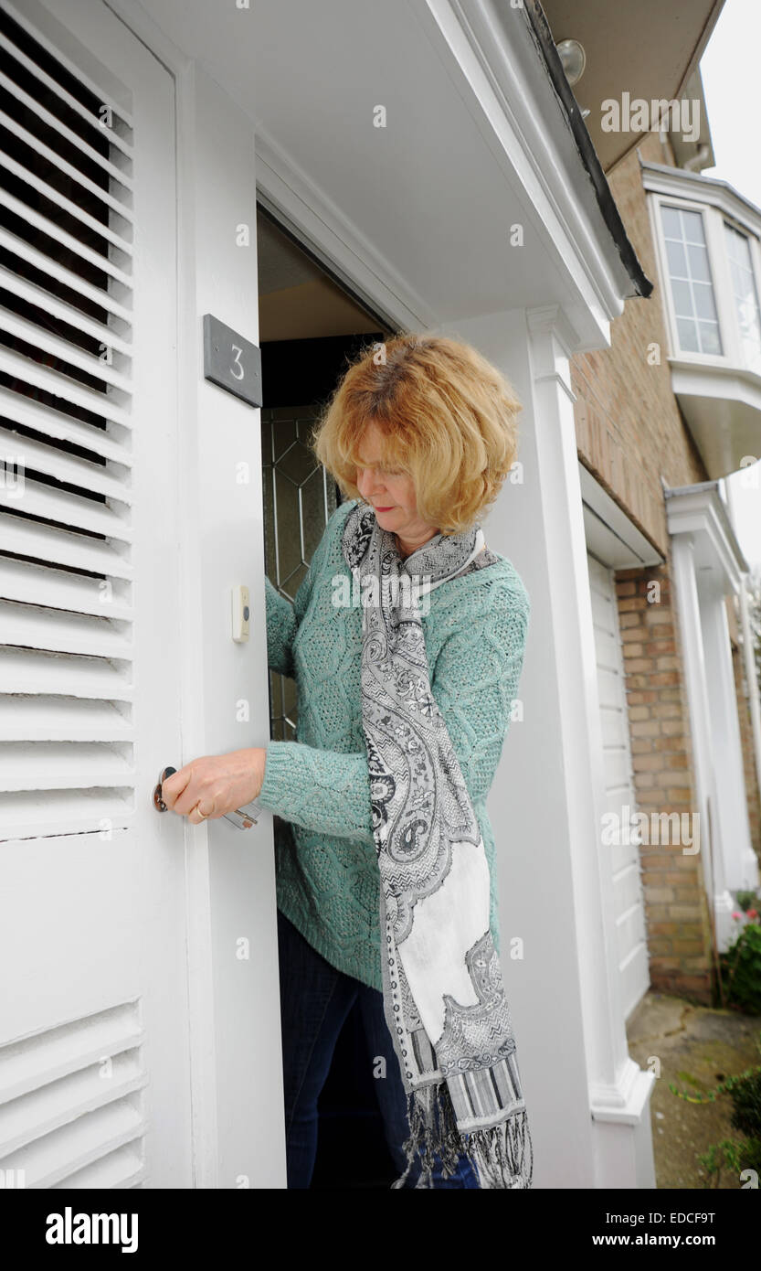 Woman looking out of her front door to greet visitors and locking ...