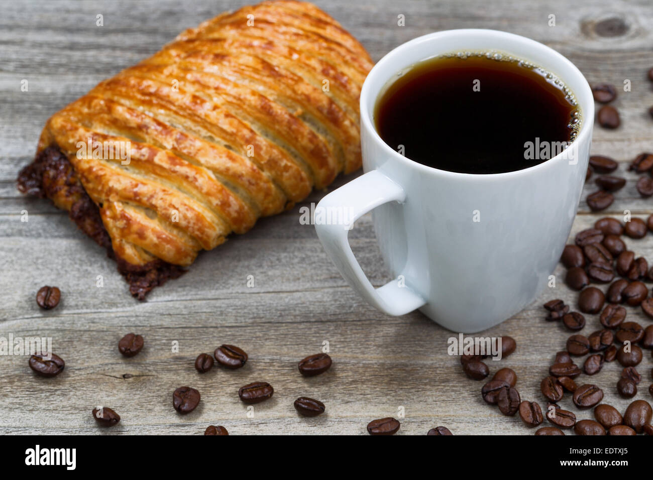 Close up of a cup of fresh dark coffee, large chocolate croissant ...