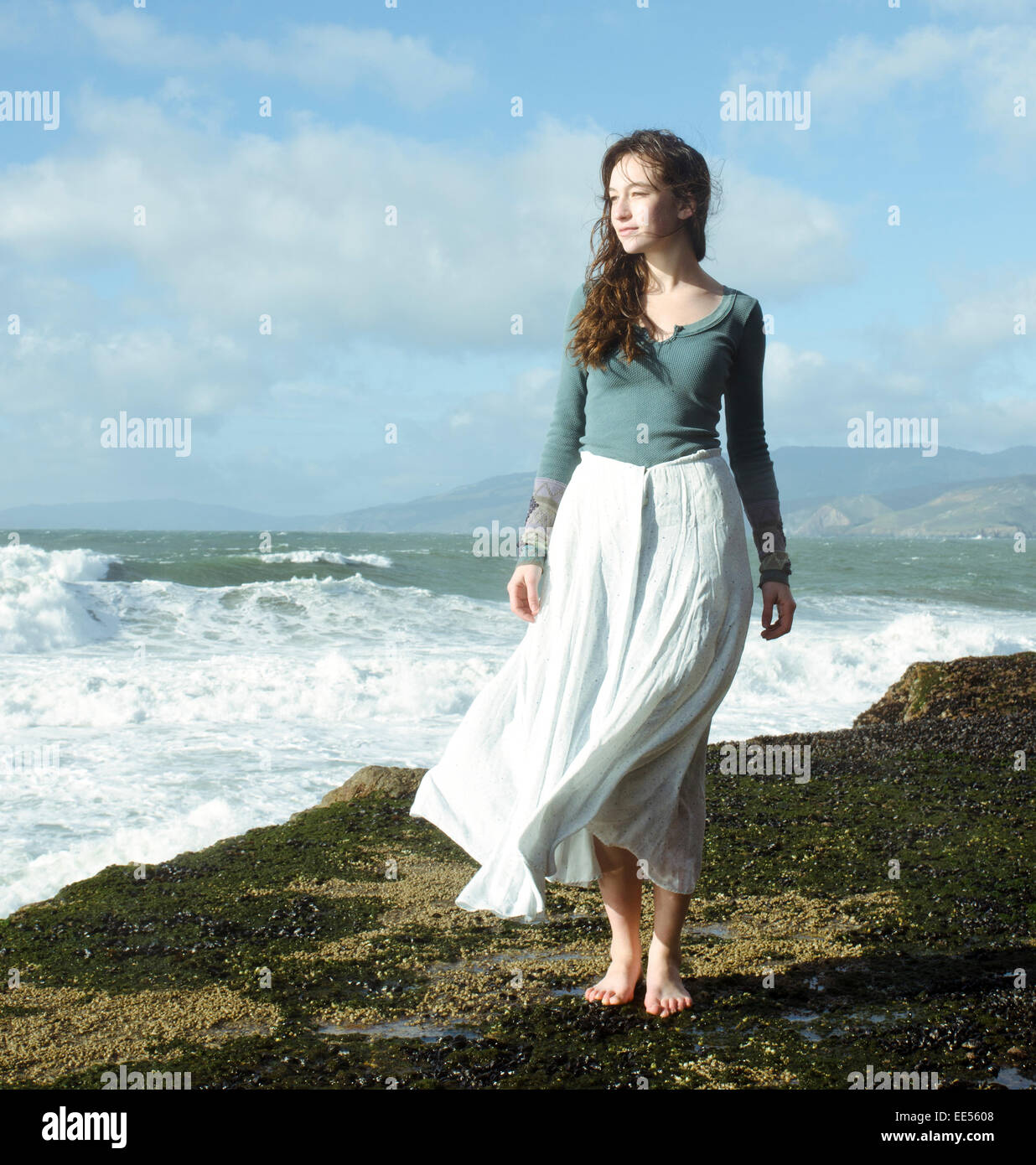 Beautiful young women with white dress in the wind looking away ...