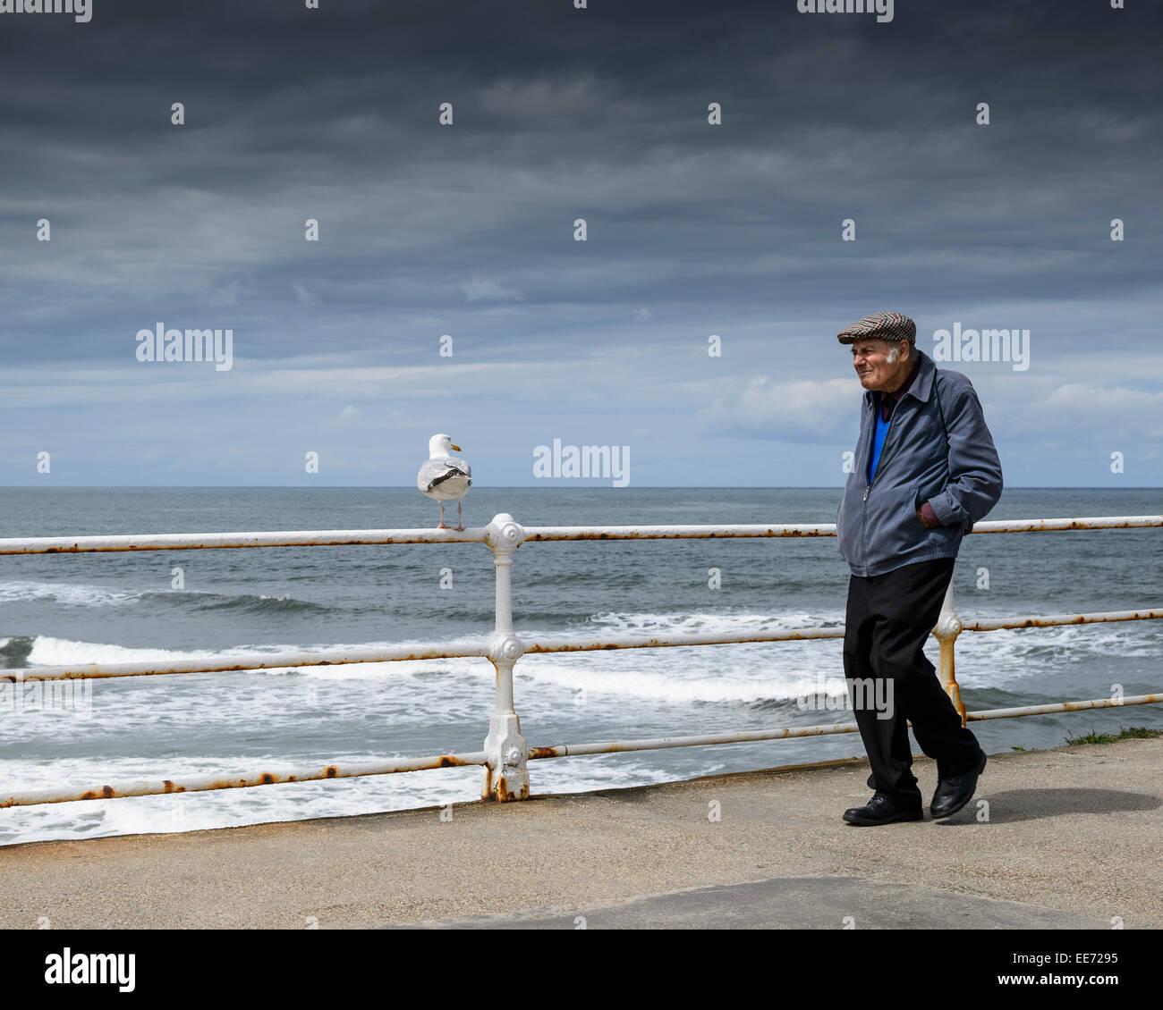 an-older-male-walking-along-whitby-pier-