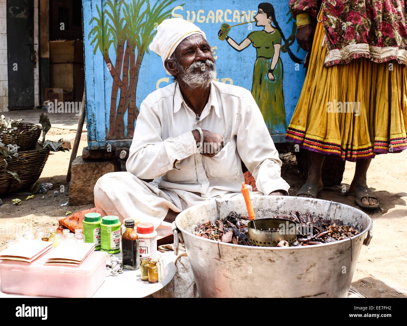 Indian herbalist selling elixir on the street in Nelamangala Stock Photo, Royalty Free Image: 77612558