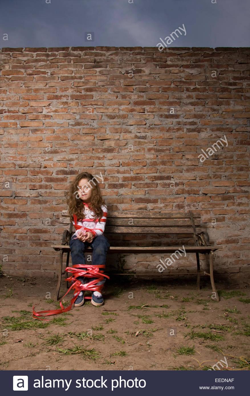 littlegirl tied up Little Girls Tied Up on Park Bench Stock Photo