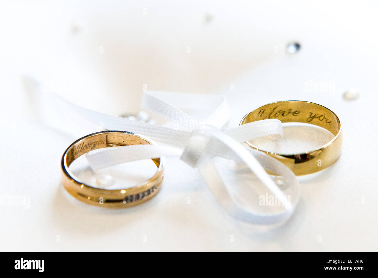 White Ribbon Joining Two Wedding Rings With I Love You Inscribed