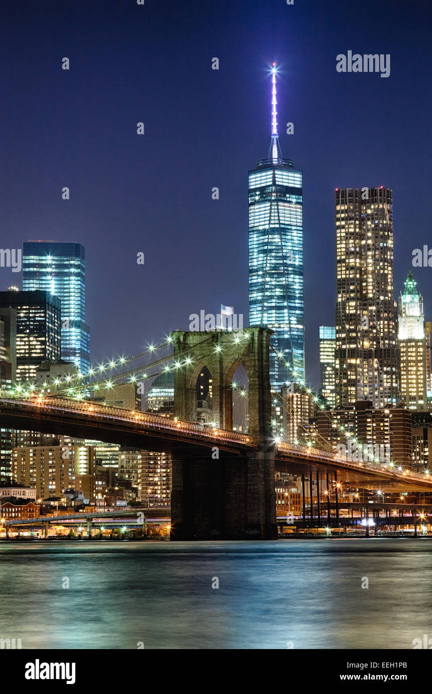 The New York City skyline at night w Brooklyn Bridge and ...