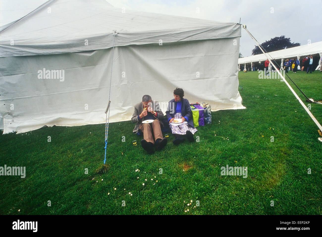 A couple having a picnic behind a marque tent at a food festival at Leeds Castle. England. UK & A couple having a picnic behind a marque tent at a food festival ...