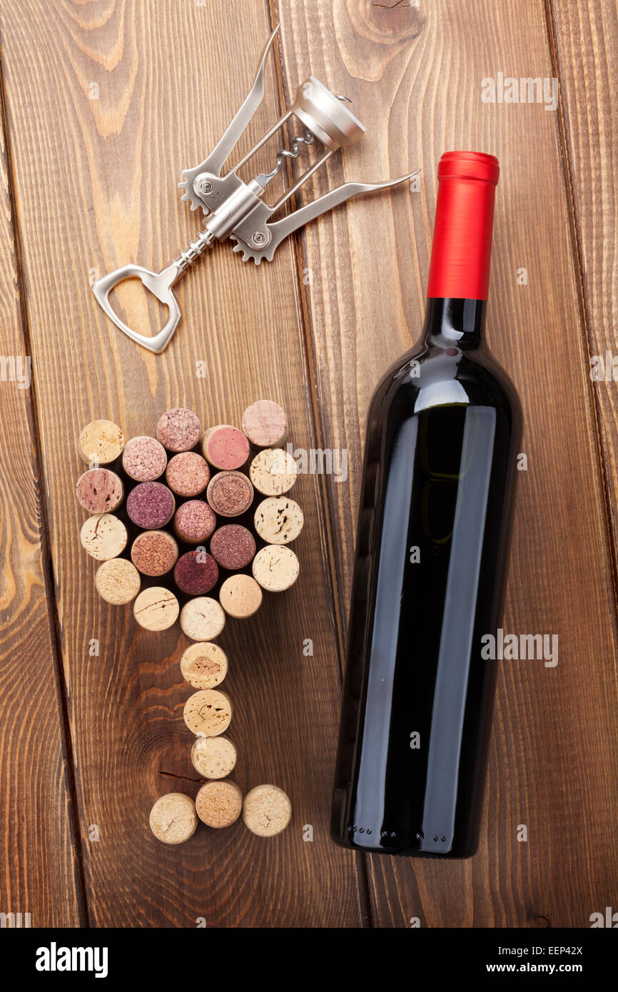 Red Wine Bottle, Glass Shaped Corks And Corkscrew. View From Above Over  Rustic Wooden Table Background