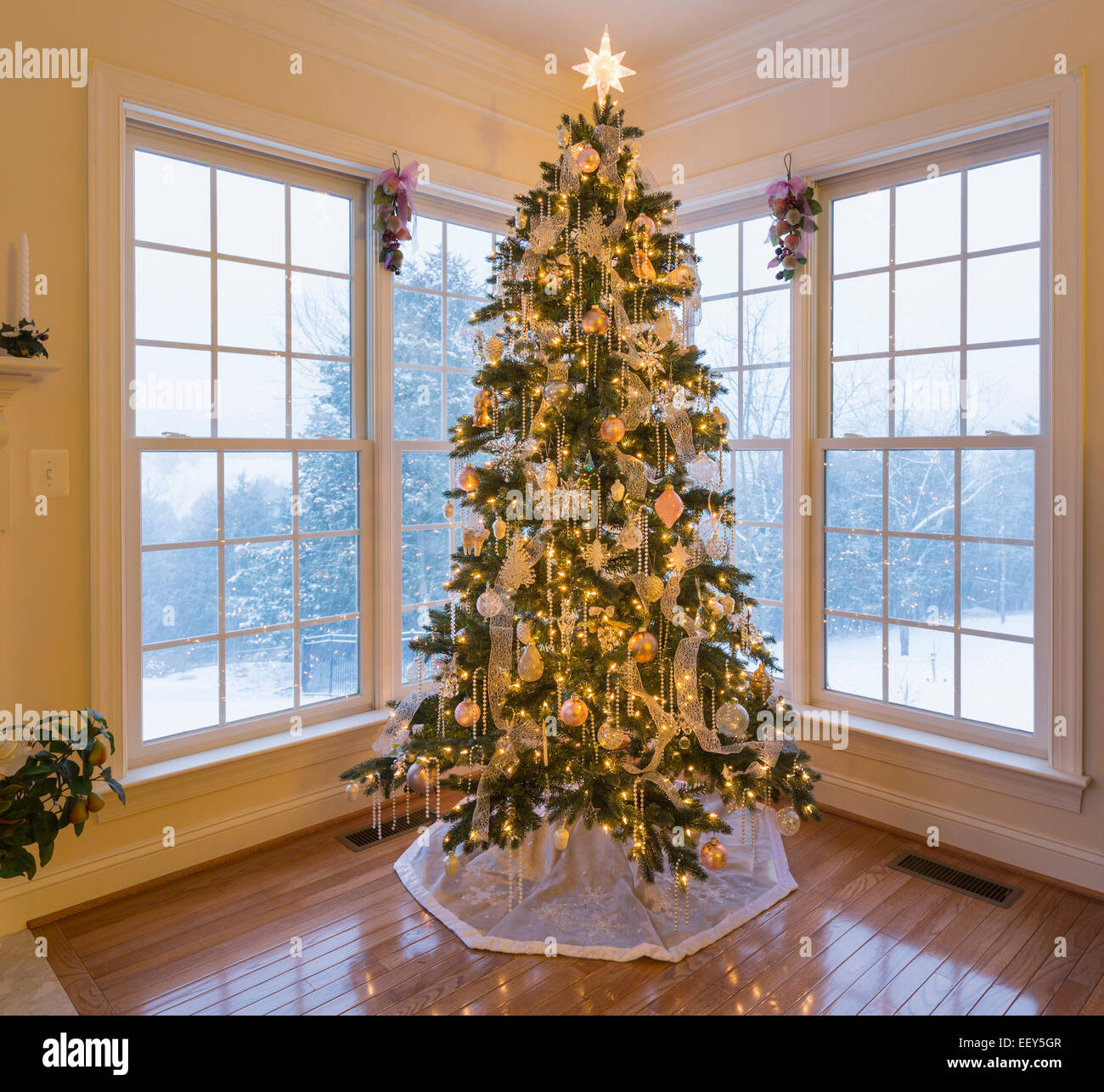 Christmas tree in modern home with snow falling outside the ...