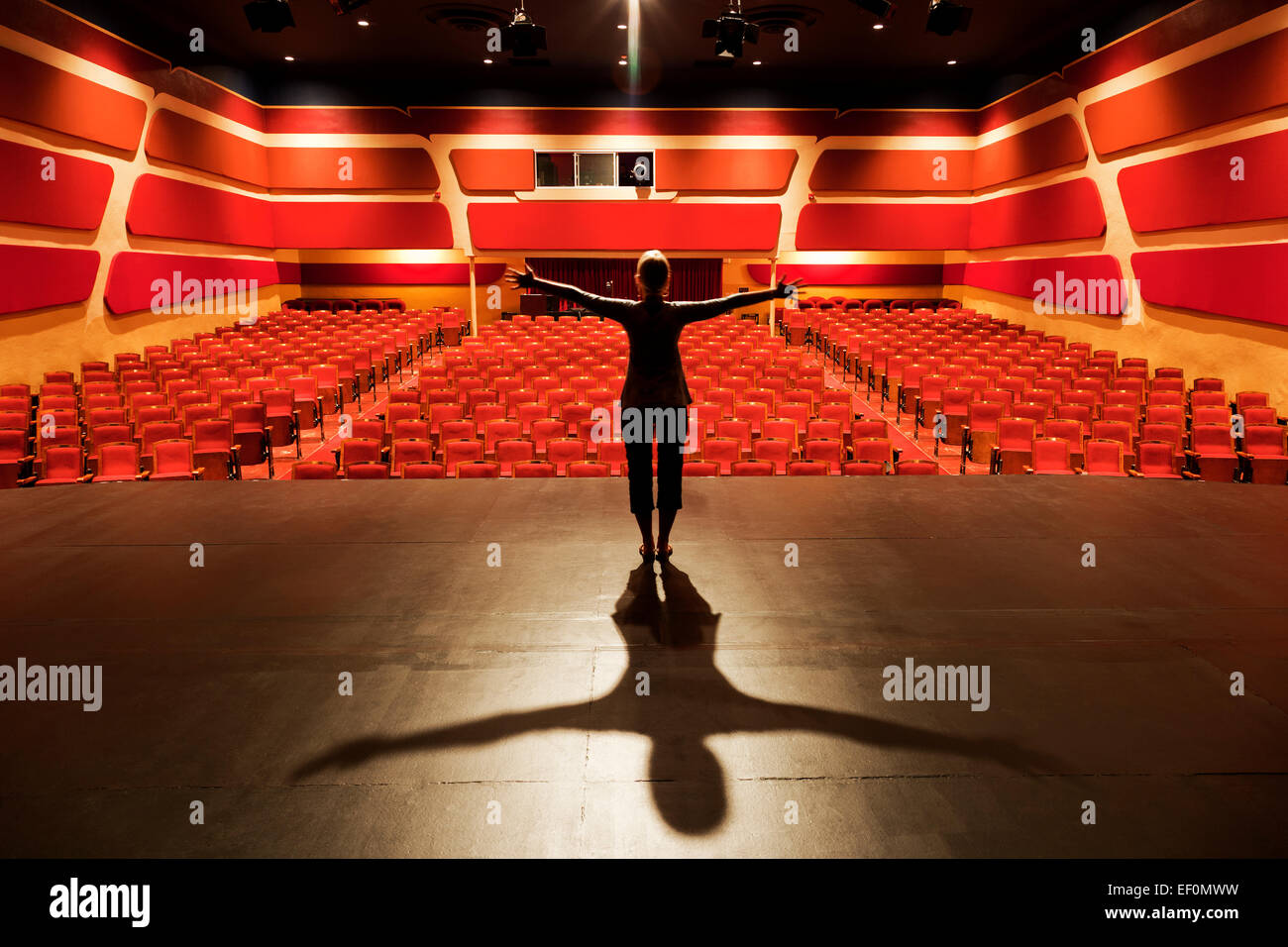 Female actor on stage in empty theater Stock Photo ...