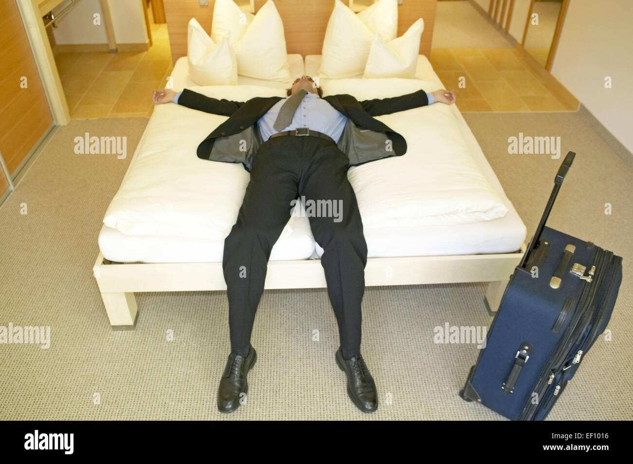 hotelzimmer mann koffer anzug liegen bett erschoepft muede kaputt stockfoto lizenzfreies bild. Black Bedroom Furniture Sets. Home Design Ideas