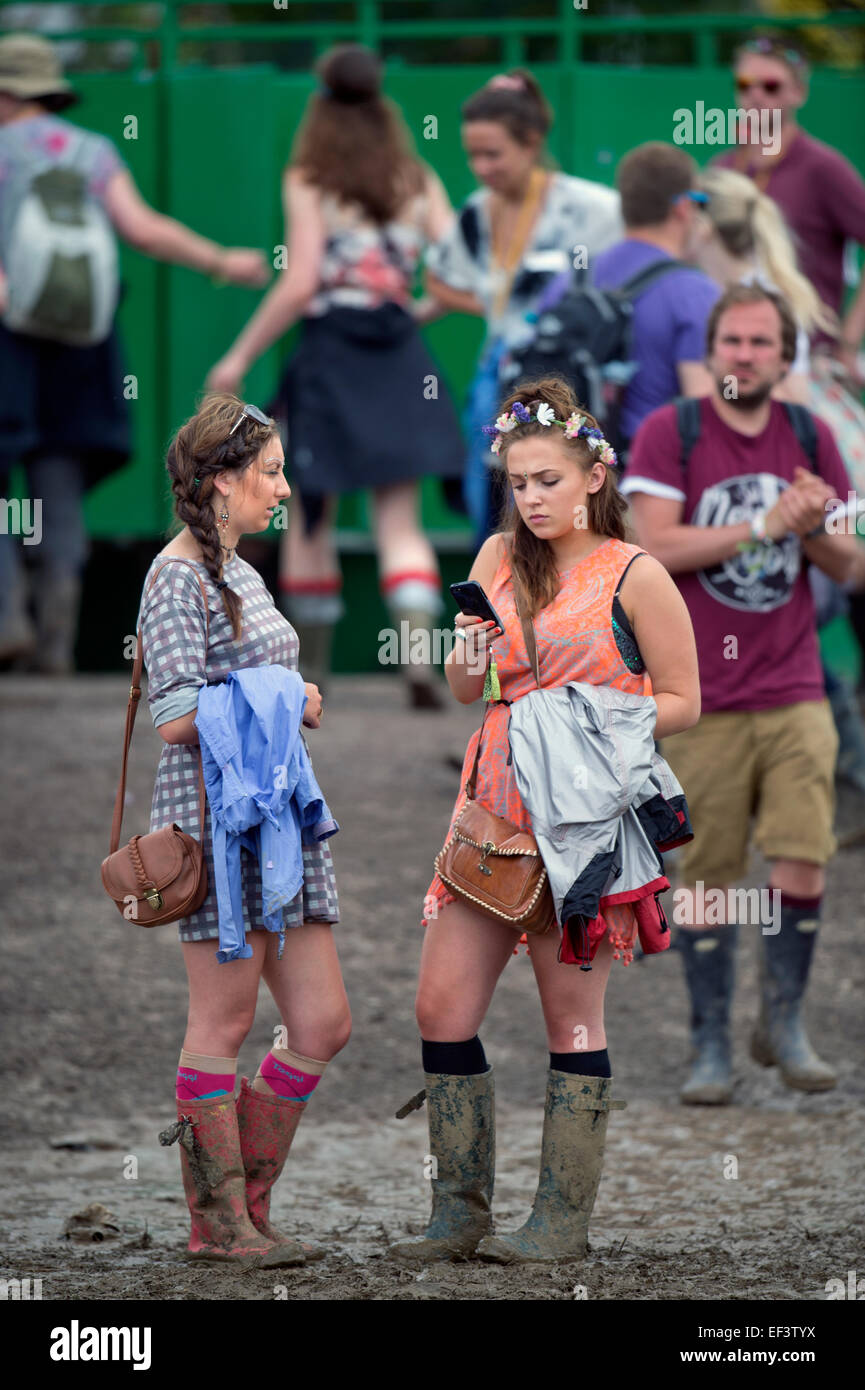 Two Girls Standing In Mud Near A Toilet Bock At The