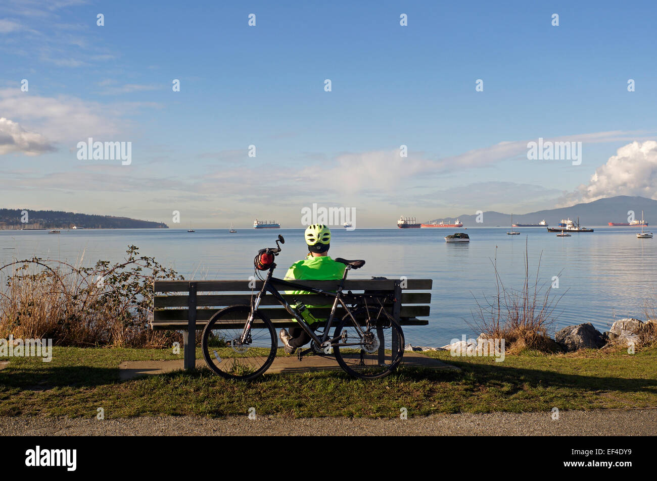 male-cyclist-sitting-on-a-park-bench-ove