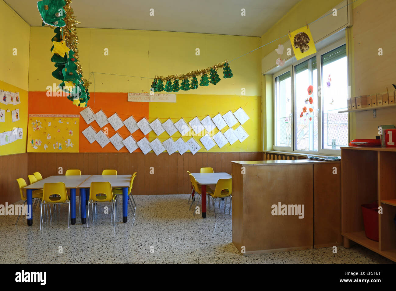 Kindergarten classroom table - Preschool Classroom With Yellow Chairs And Table With Drawings Of Children Hanging On The Walls