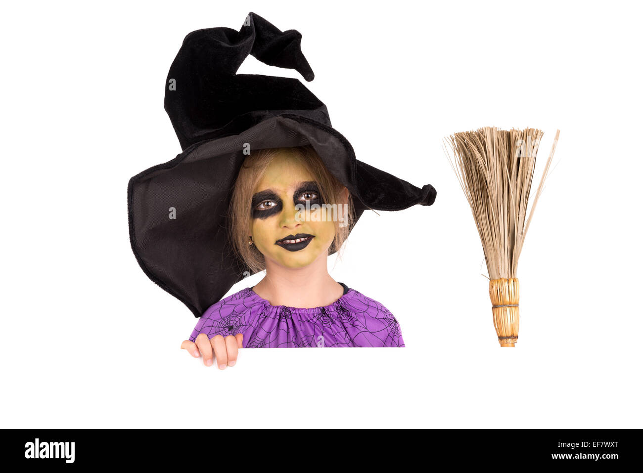 Girl with face-paint and Halloween witch costume over a white ...