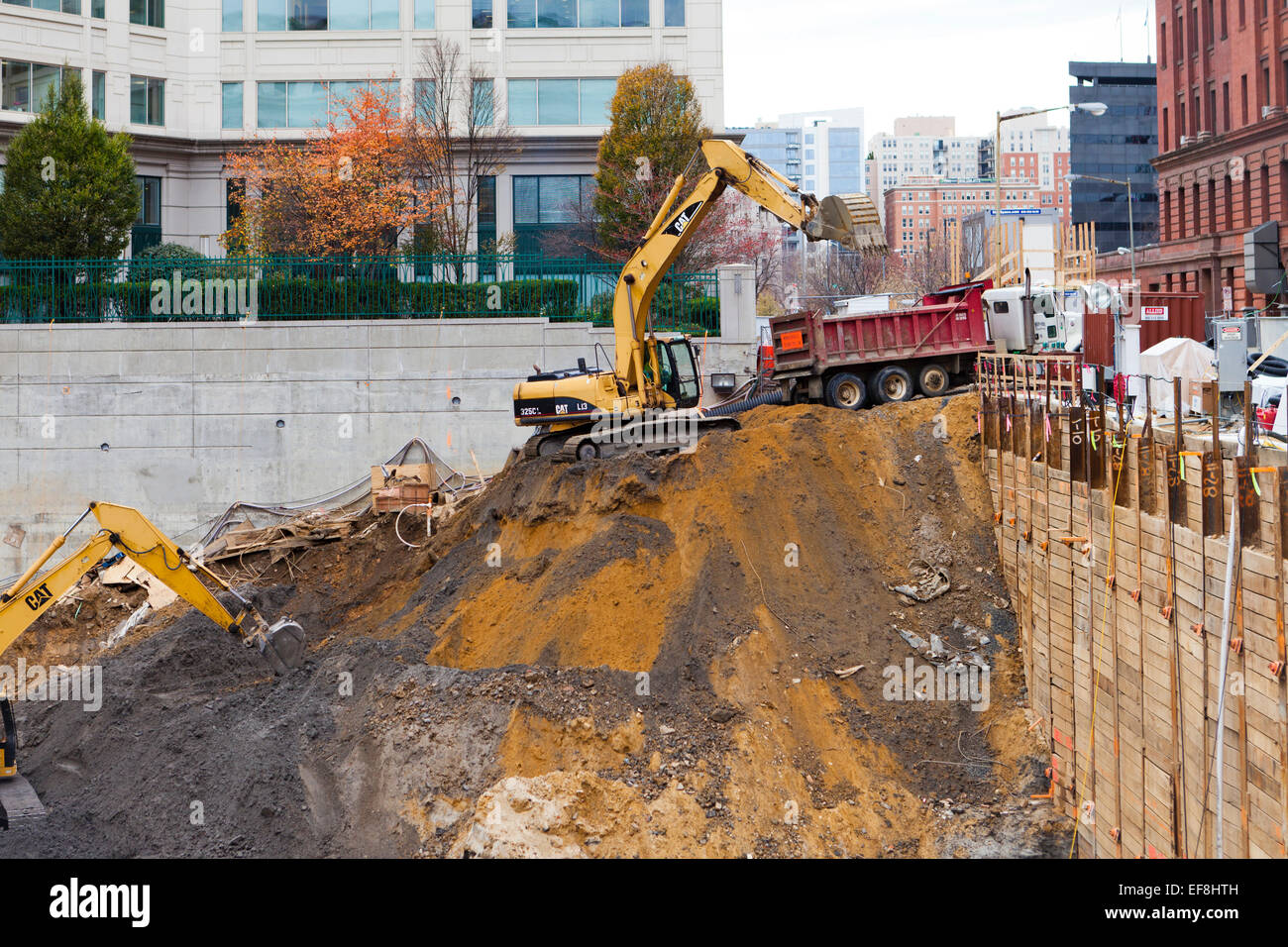 Excavators digging foundation at construction site usa for Digging foundation for house