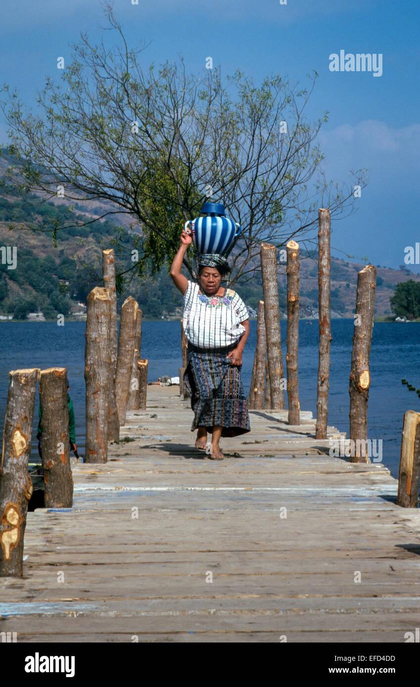 A woman walks along a jetty next to lake atitlan carrying a vase a woman walks along a jetty next to lake atitlan carrying a vase on her head reviewsmspy