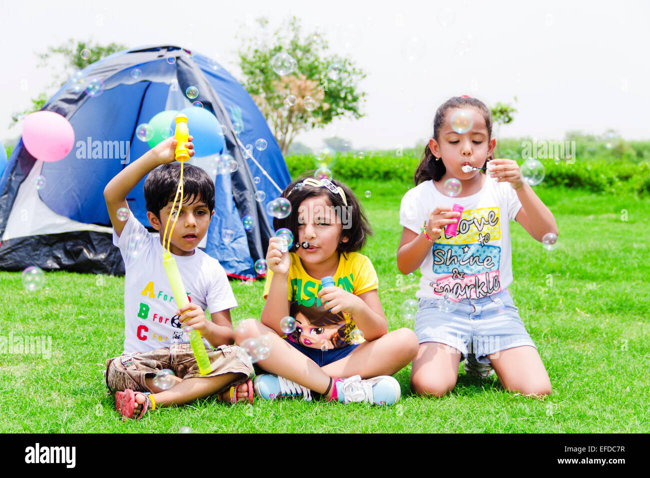 3 indian children friends Picnic park playing Bubble Wand ...