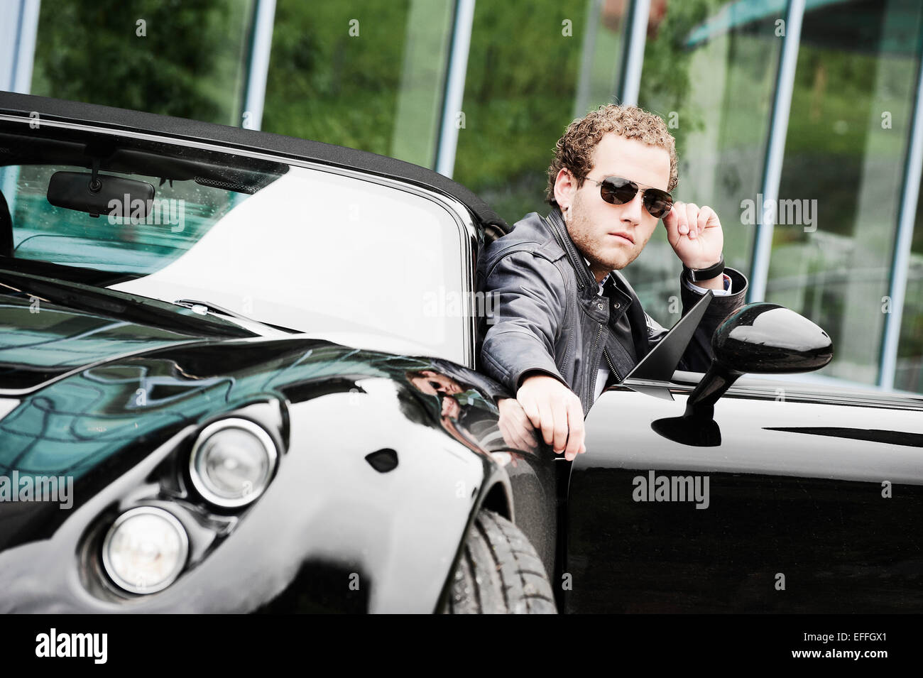 Young Man Wearing Sunglasses Sitting In Black Sports Car Stock   Cool Cars  For Young Guys