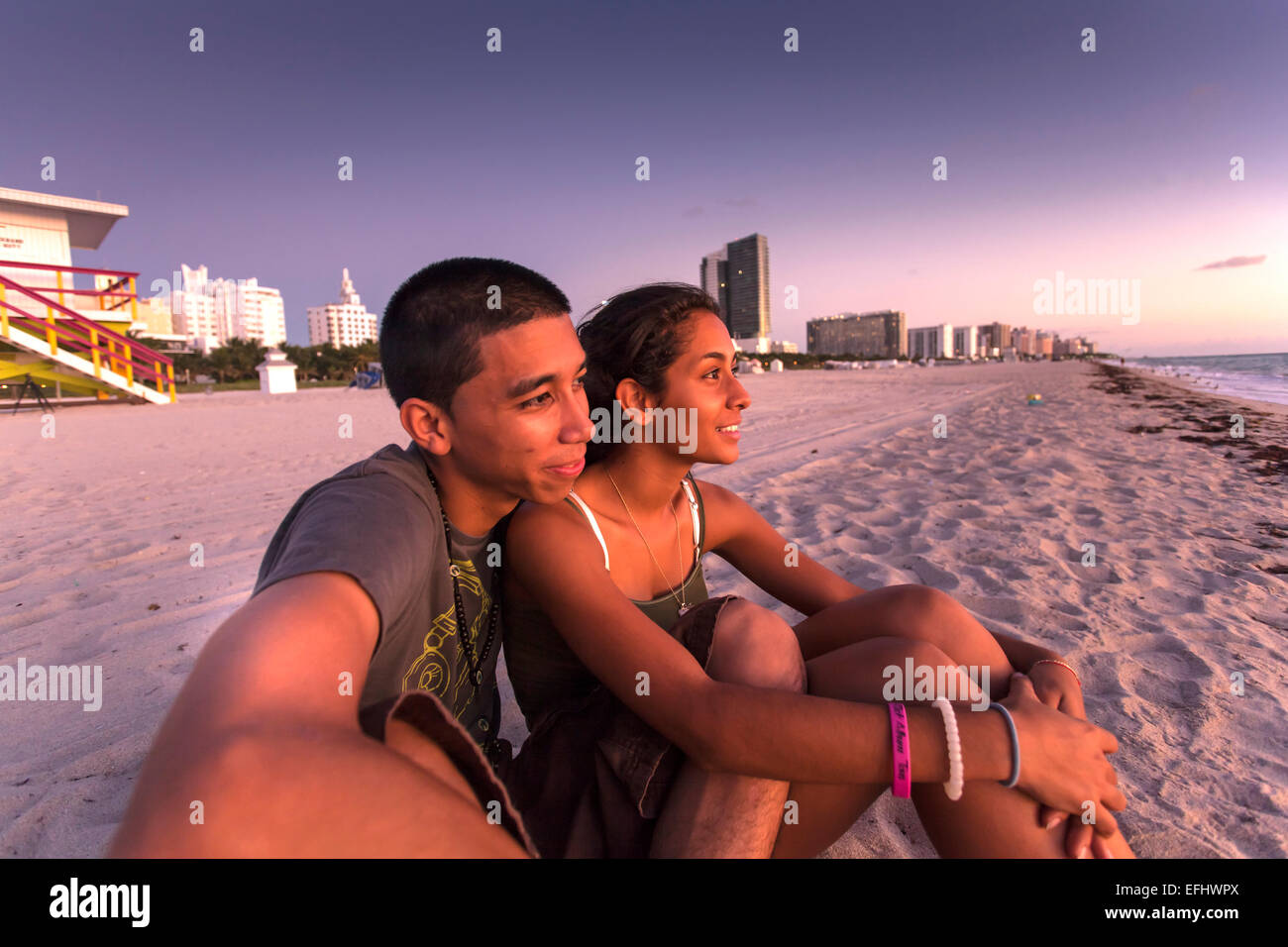 Young Latino Couple Watching The Sunrise On Beach South Miami Florida USA