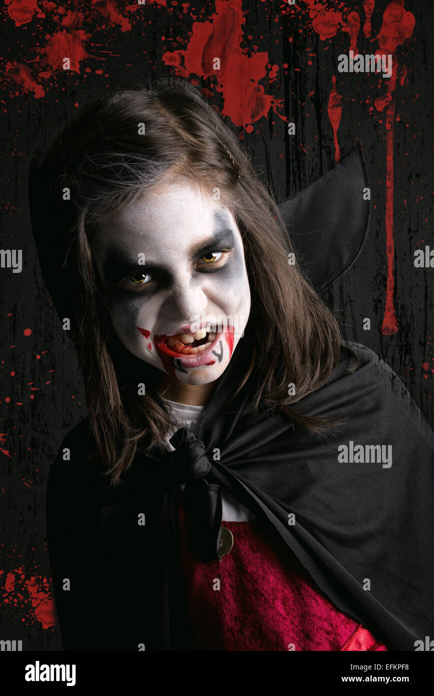 Girl with face-paint and Halloween vampire costume in a dark ...