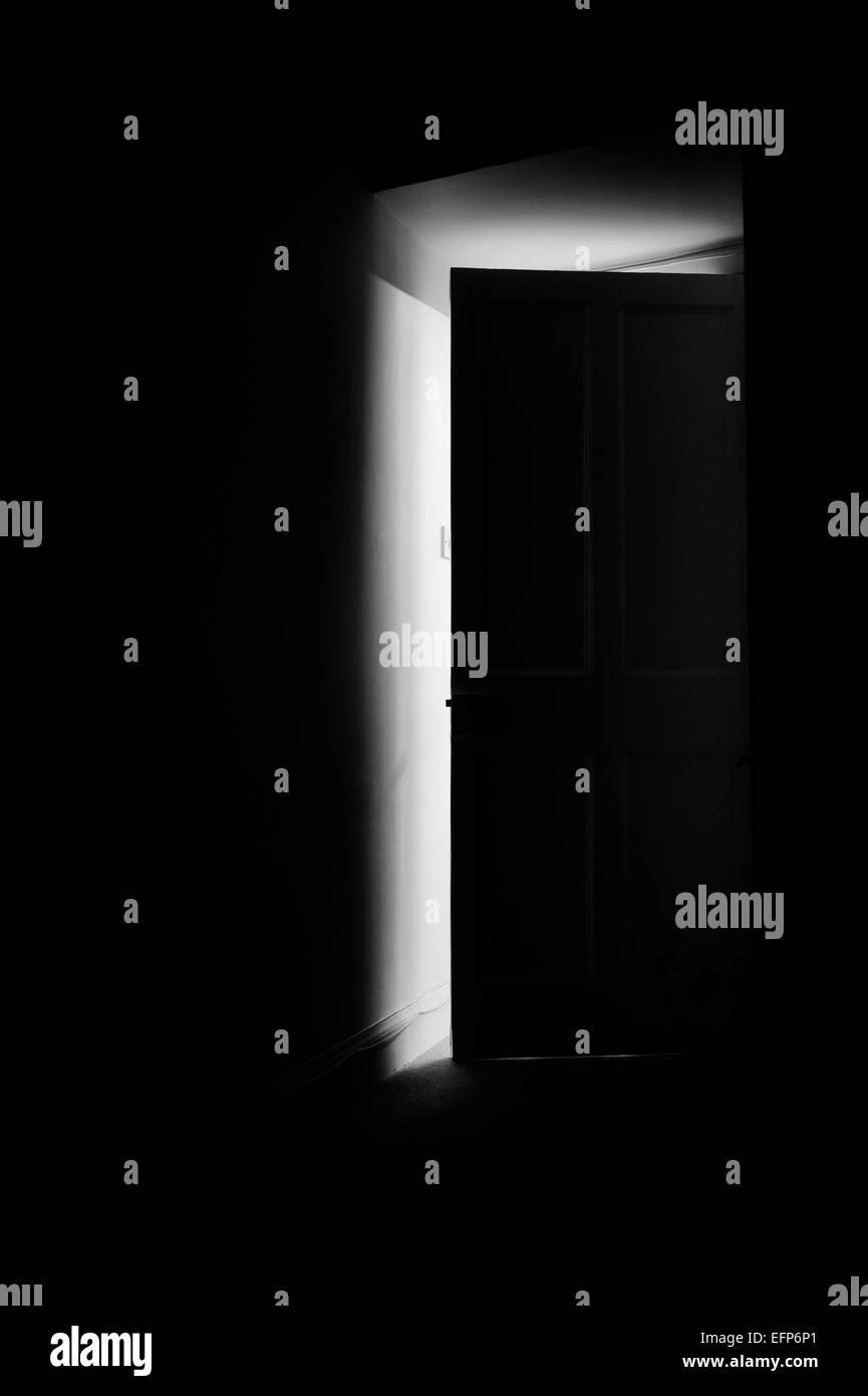Light coming through an open door into a dark room at night Stock