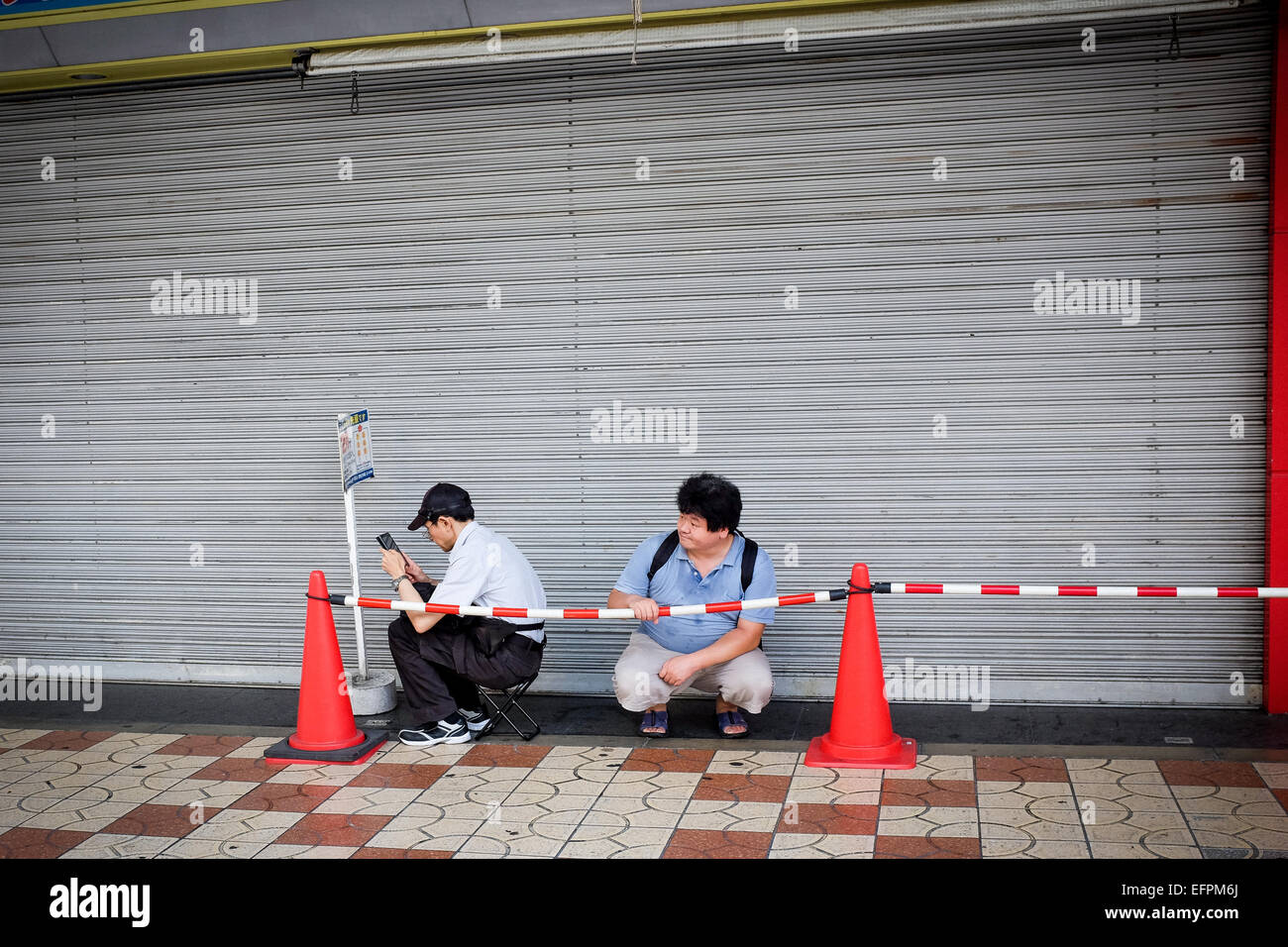 Two people form a short queue in Osaka, Japan Stock Photo, Royalty ...