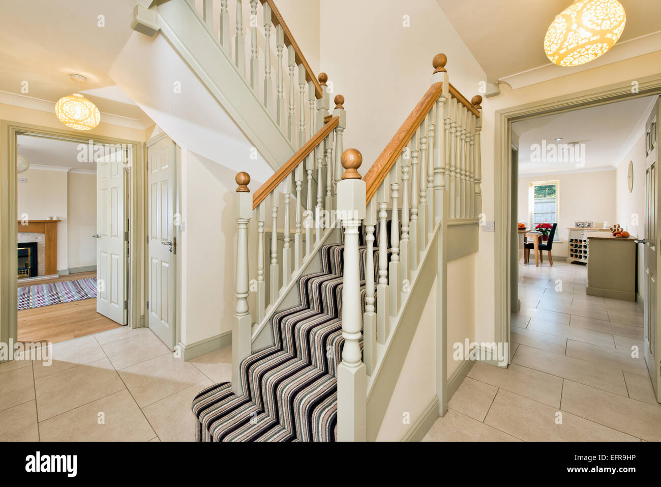 A Tidy Entrance Hallway Stairs In Typical Modern UK Home Leading To Kitchen Living Room