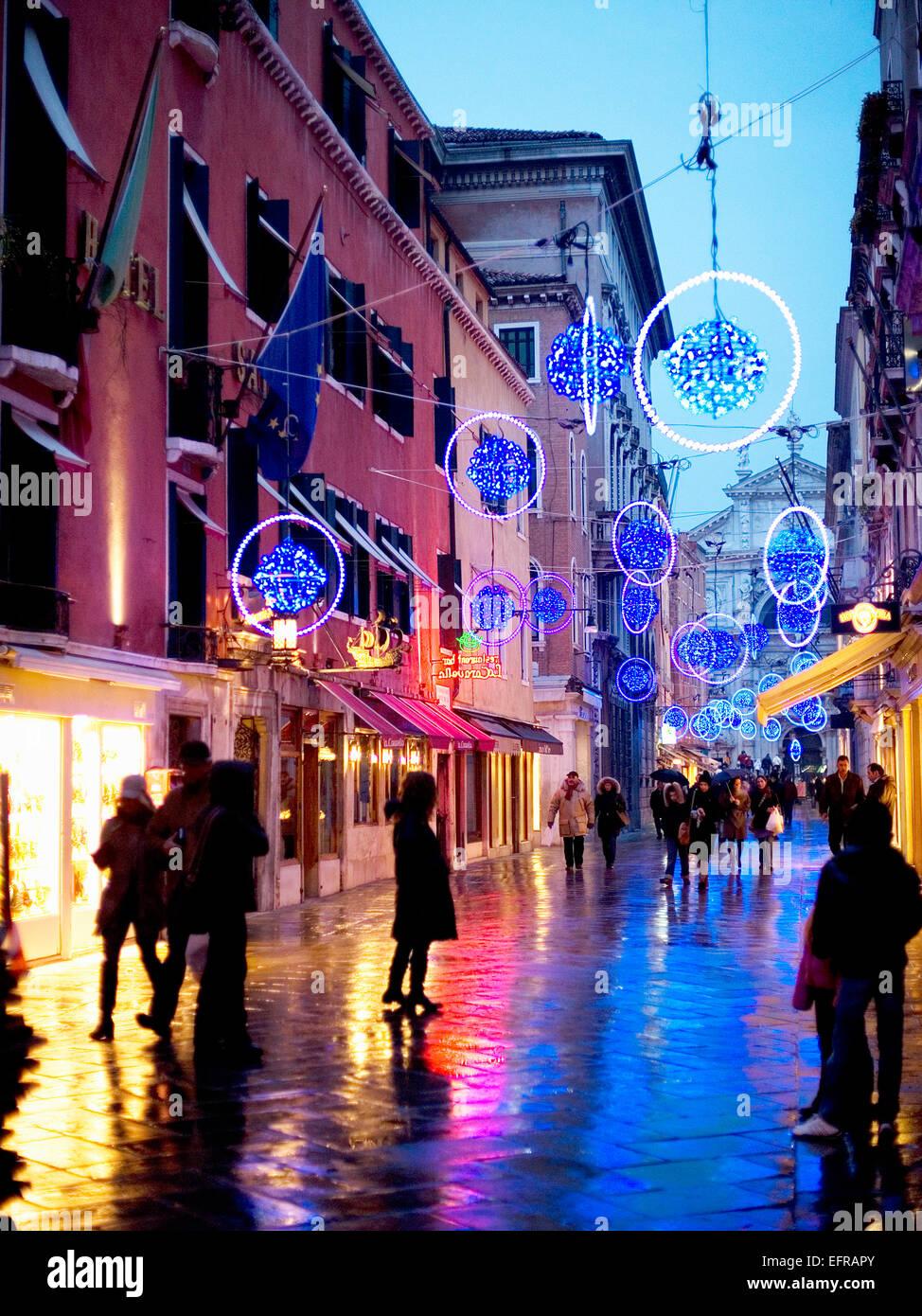 People walking in a narrow street at night. Street lights ...