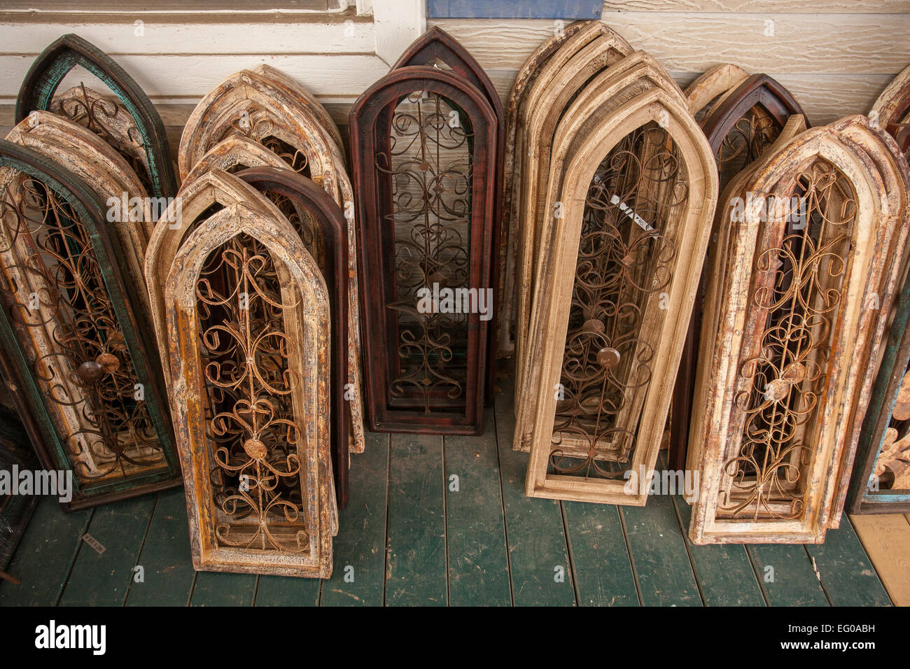 Stacks of rustic window shutters with metal scrolled decorations displayed  at home decorative accessories store