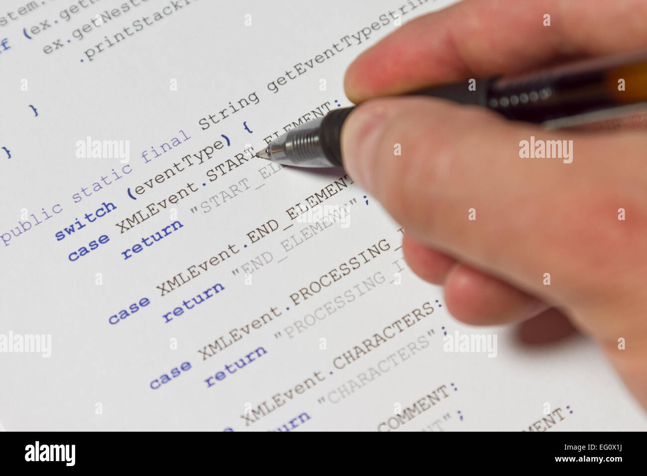 A programmer man pointing with his pen at Java computer code – Xml Programmer