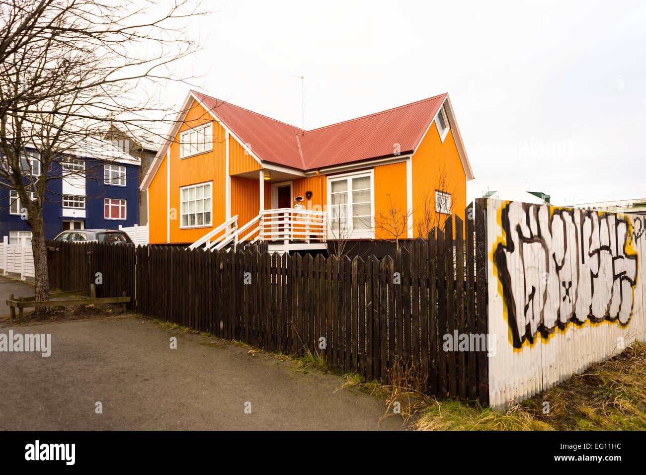 An Orange And Red Painted House Surrounded By A Fence With Graffiti Around  In Reykjavik, Iceland, 2014.