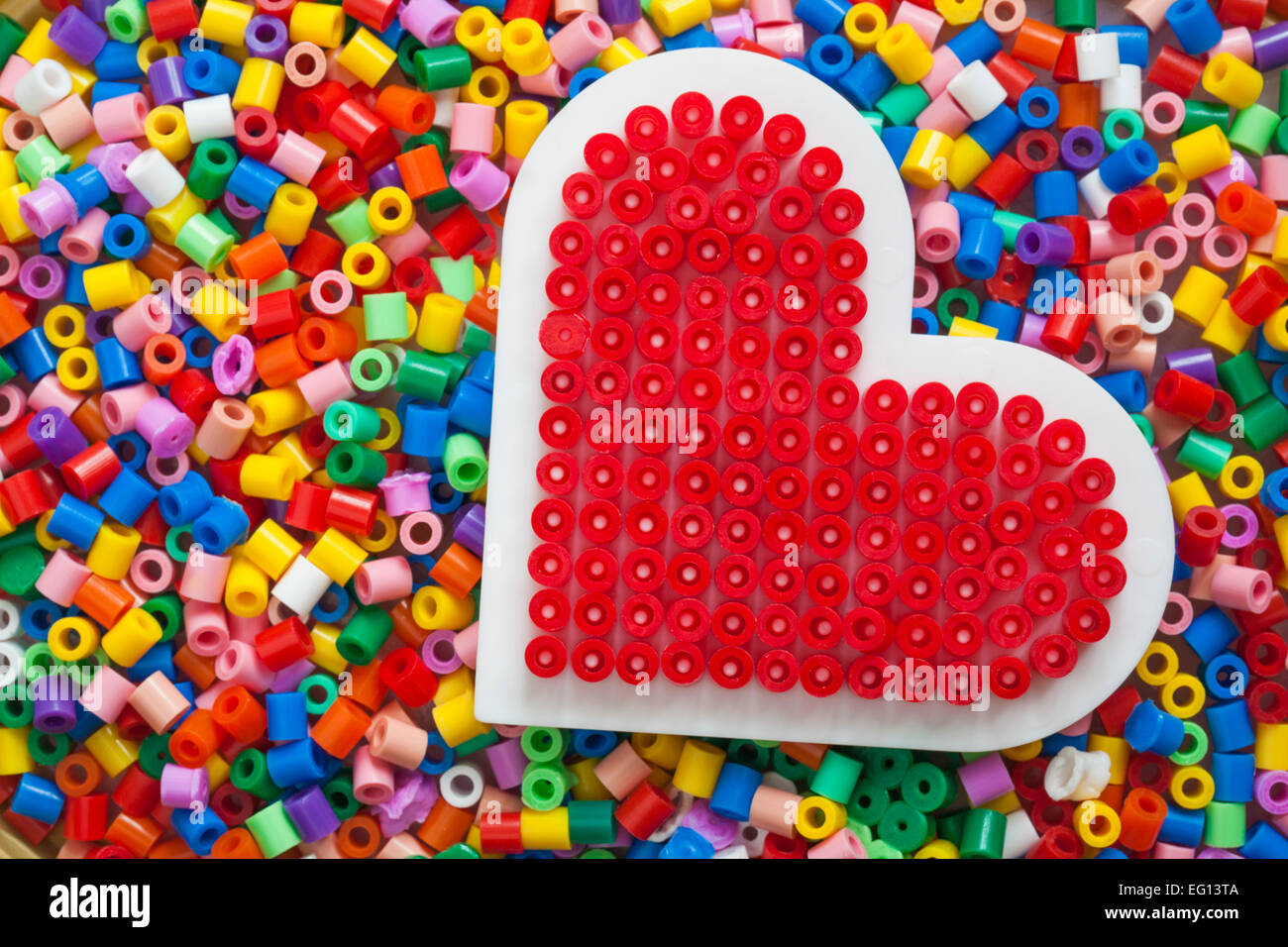 Plastic beads for crafts - Stock Photo Plastic Multi Coloured Hama Beads With Red Heart Completed Template For Crafts