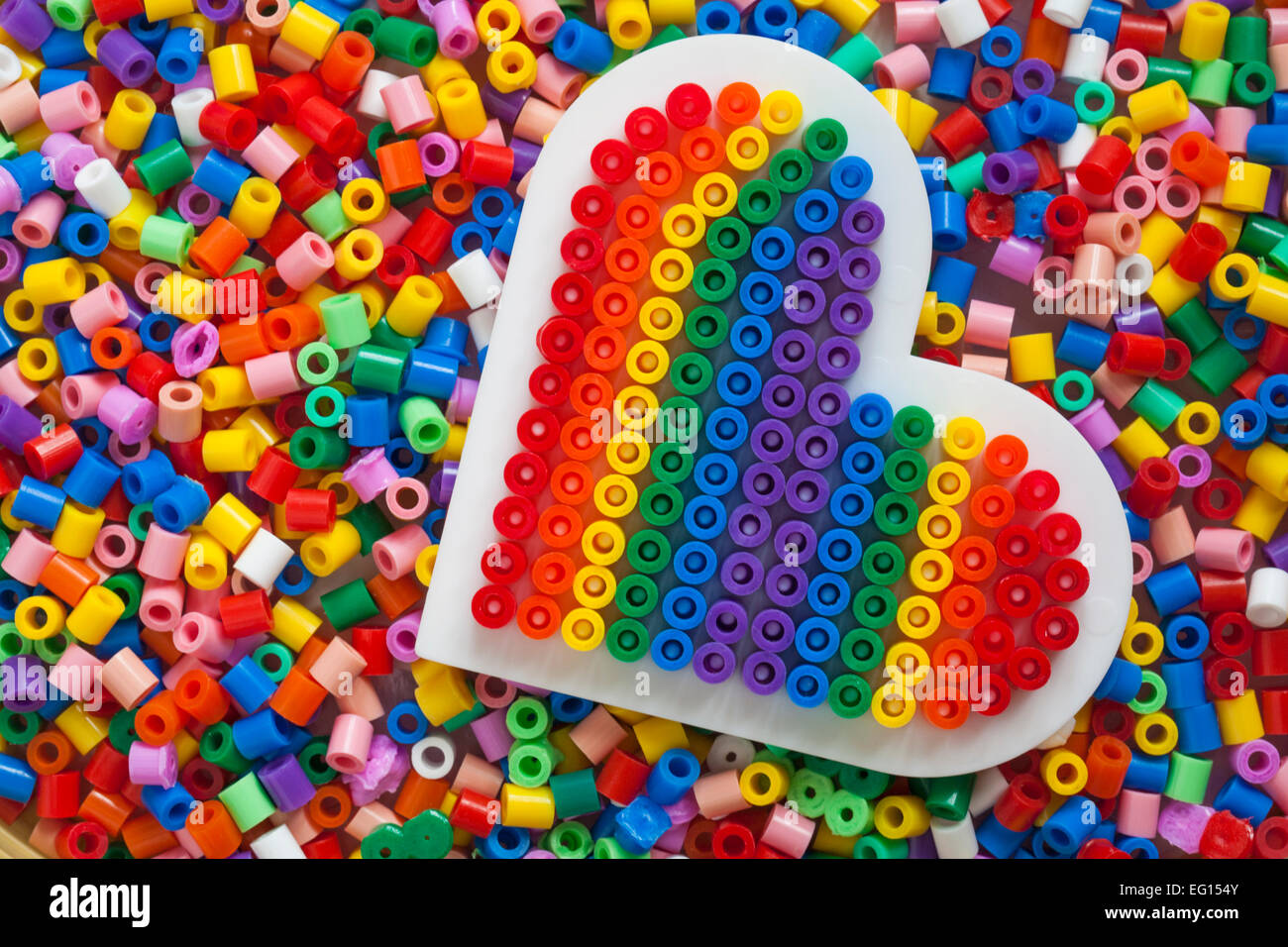 Plastic beads for crafts - Stock Photo Plastic Multi Coloured Hama Beads With Rainbow Heart Completed Template For Crafts