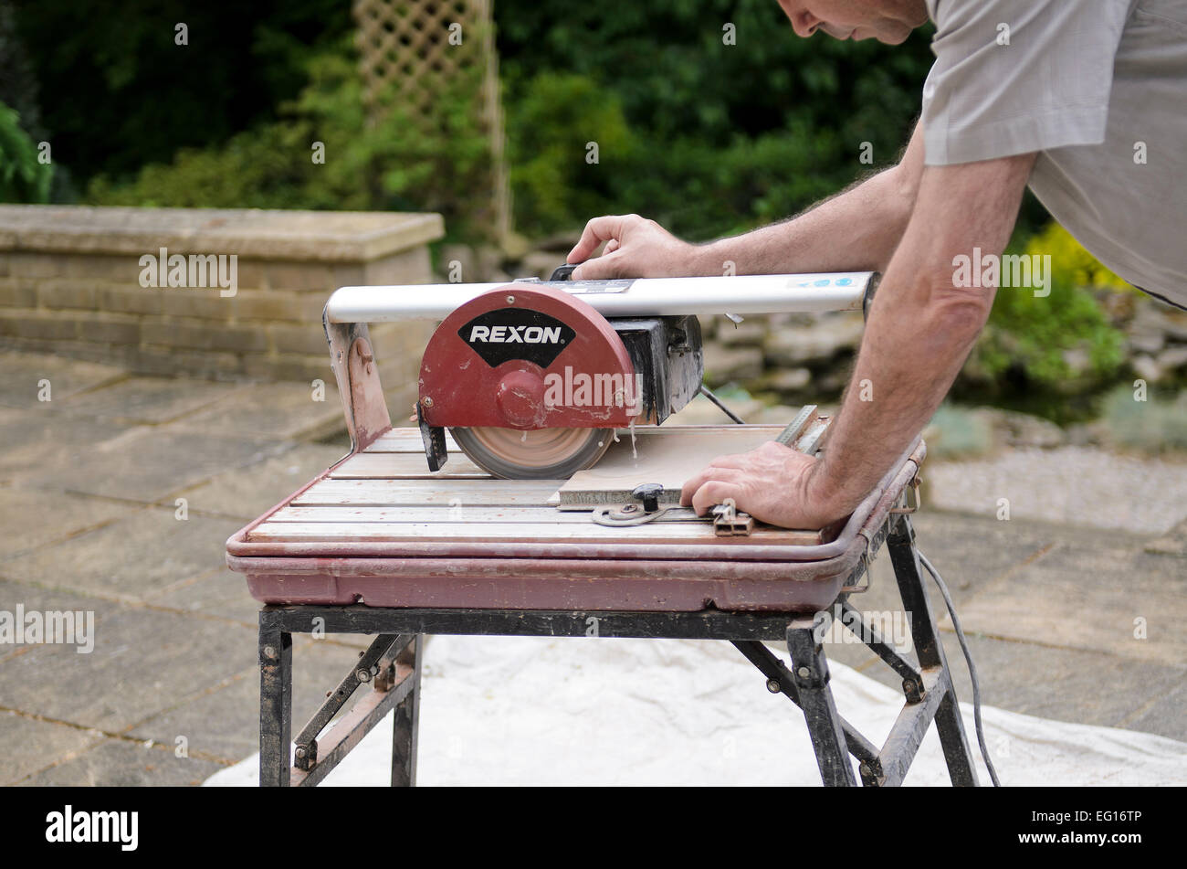Man using water cooled ceramic tile cutting machine release stock photo man using water cooled ceramic tile cutting machine release available dailygadgetfo Gallery