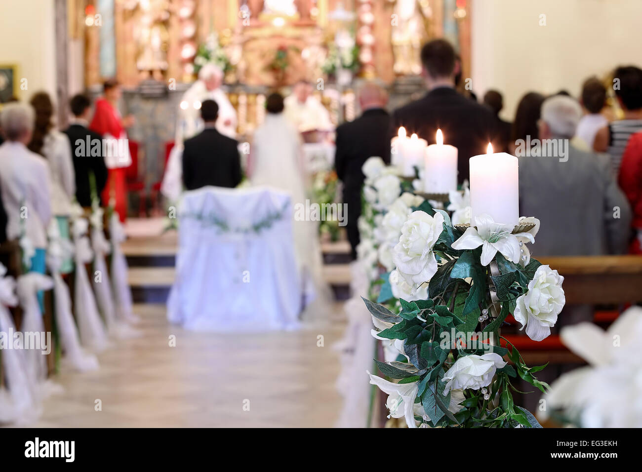 Young Couple During The Wedding Ceremony Before Altar In A Church Full Of People