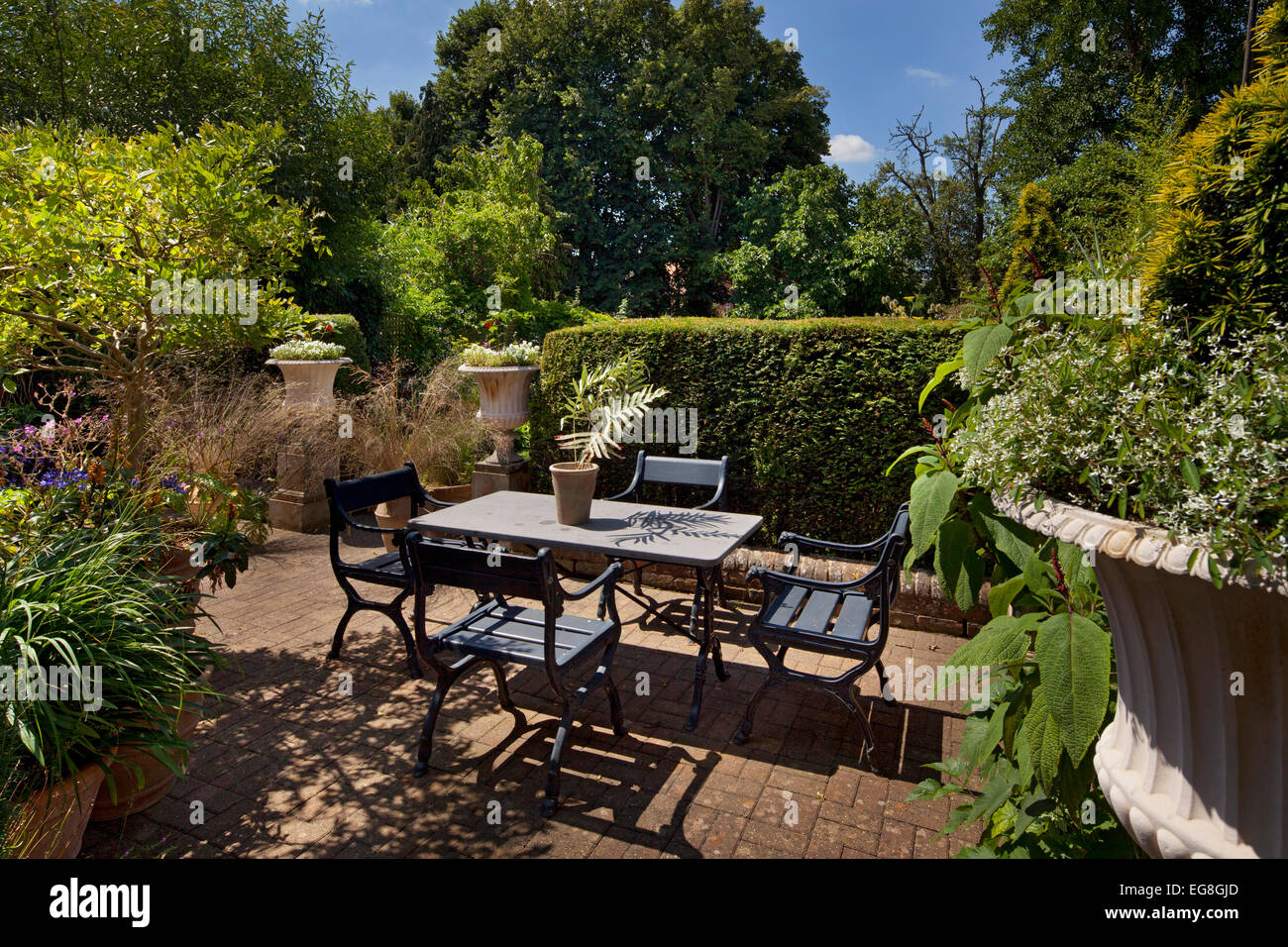 Formal Outdoor Seating Area With Large Urns Stone Table And Brick Patio In  English Garden,Oxfordshire,England