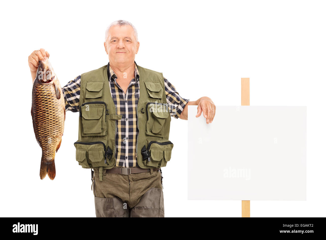 smiling mature fisherman holding a big fish next to a panel isolated