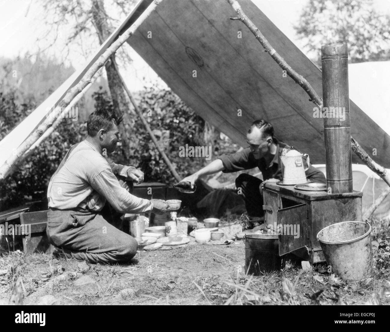 1920s TWO MEN EATING UNDER A FRAME TENT CANVAS TARP VICTUALS PROVISIONS COFFEE POT ON BLACK CAMP STOVE ADVENTURE ROUGHING IT & 1920s TWO MEN EATING UNDER A FRAME TENT CANVAS TARP VICTUALS Stock ...