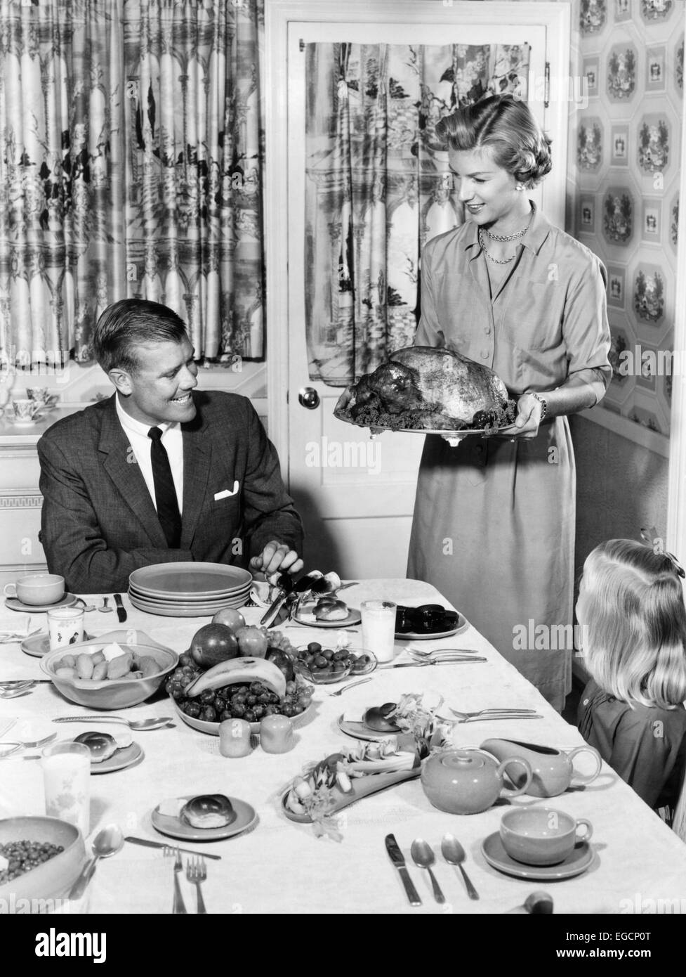 1950s THANKSGIVING FAMILY AT DINING ROOM TABLE MOM HOLDING TURKEY ON PLATTER PRINT CURTAINS SETTING WALLPAPER