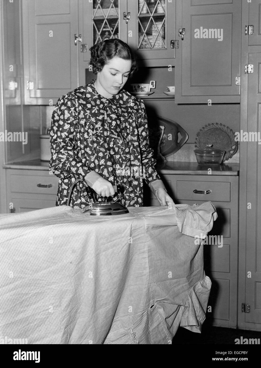 White apron cape town -  1930s 1940s Woman Wearing Printed Smock Apron Standing Ironing Board Pushing Electric Iron Stock Photo