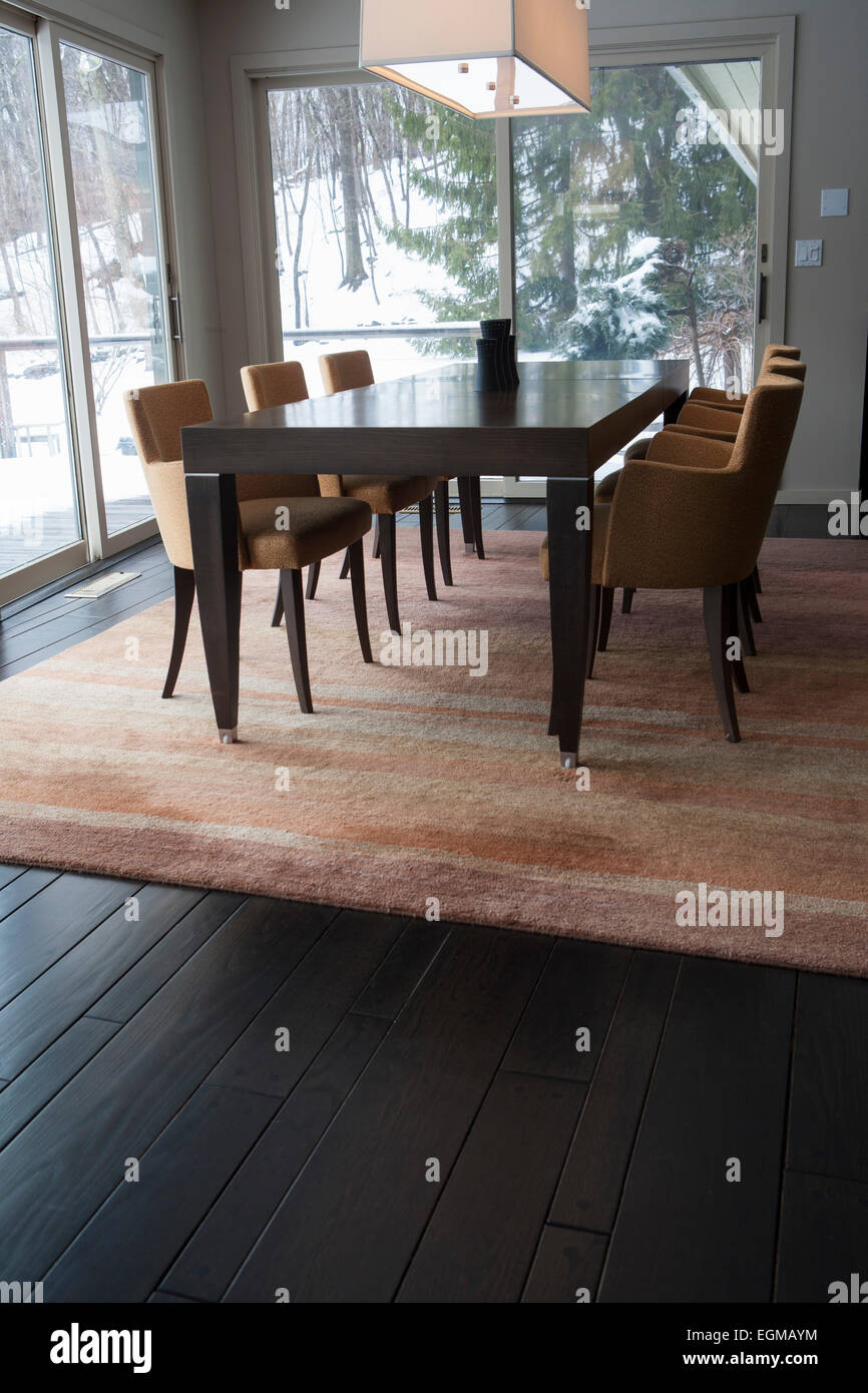 Dining Room Table With Upholstered Orange Chairs On Area Rug And Dark Wood Floor