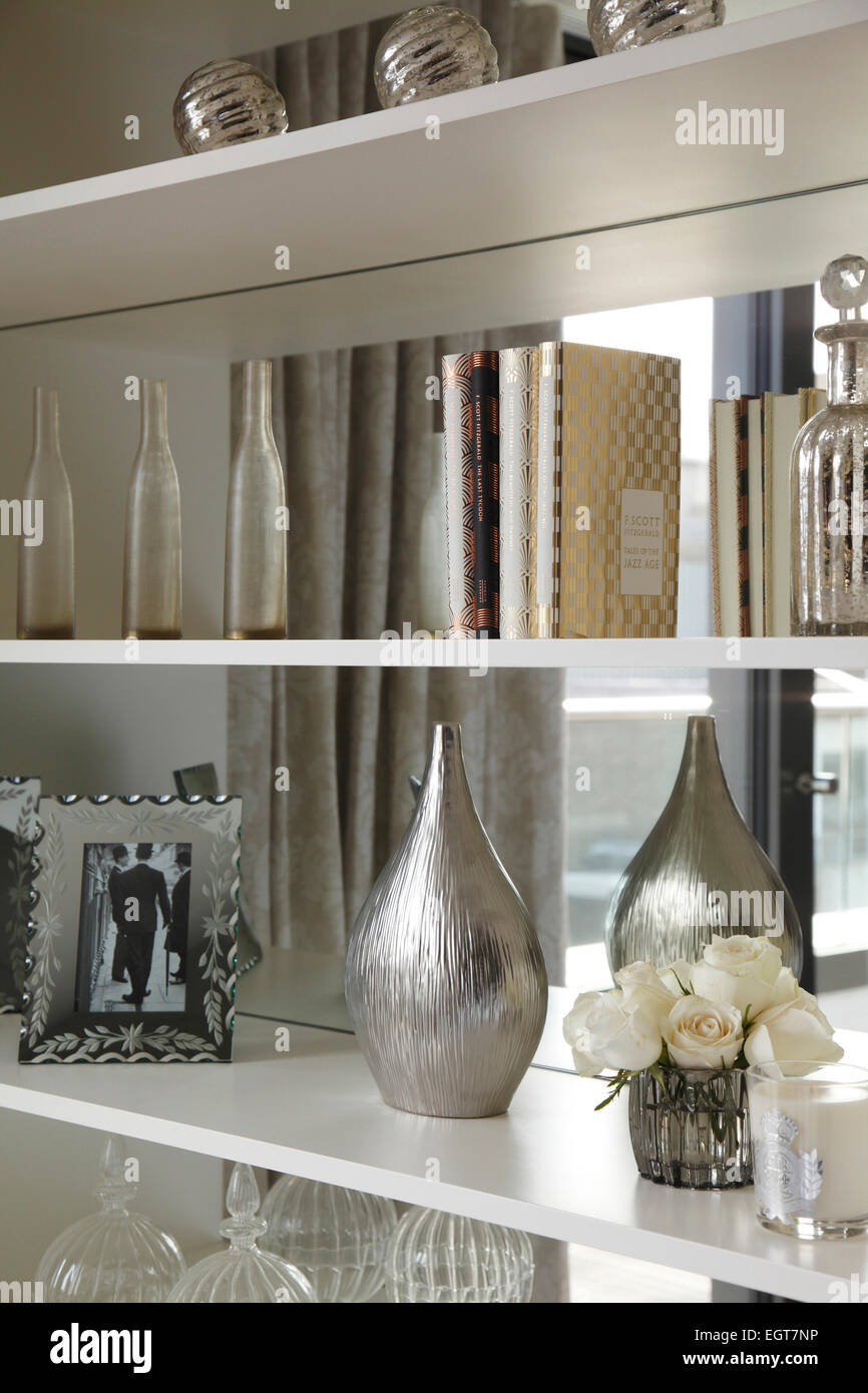 Decorative objects, books and a vase of white roses arranged on shelves in  mirrored recess in UK show home
