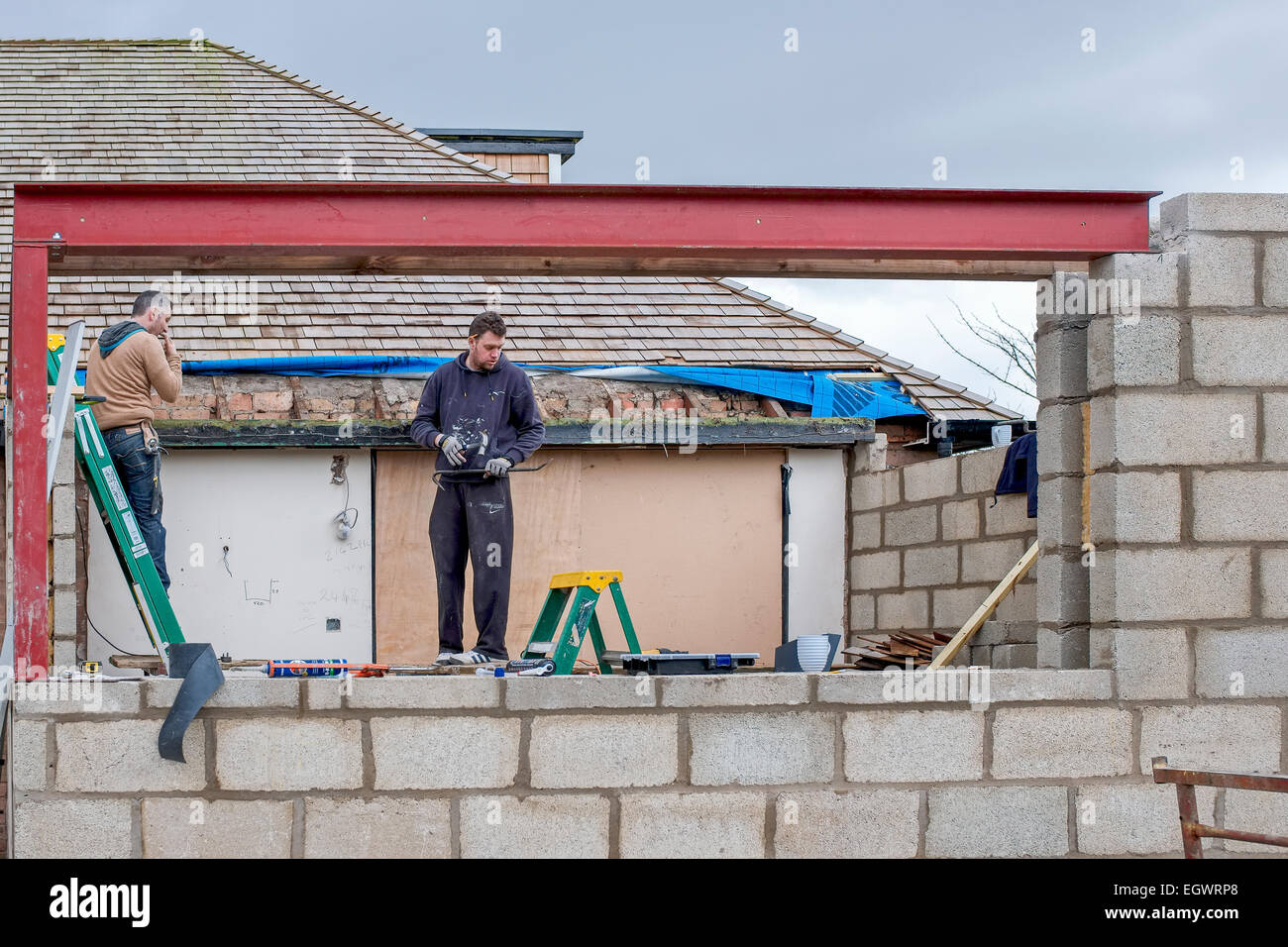 Two Workmen Building A House Extension Stood On A