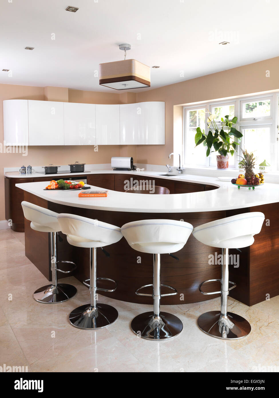 bar stools at breakfast bar in modern kitchen uk home stock photo  - bar stools at breakfast bar in modern kitchen uk home