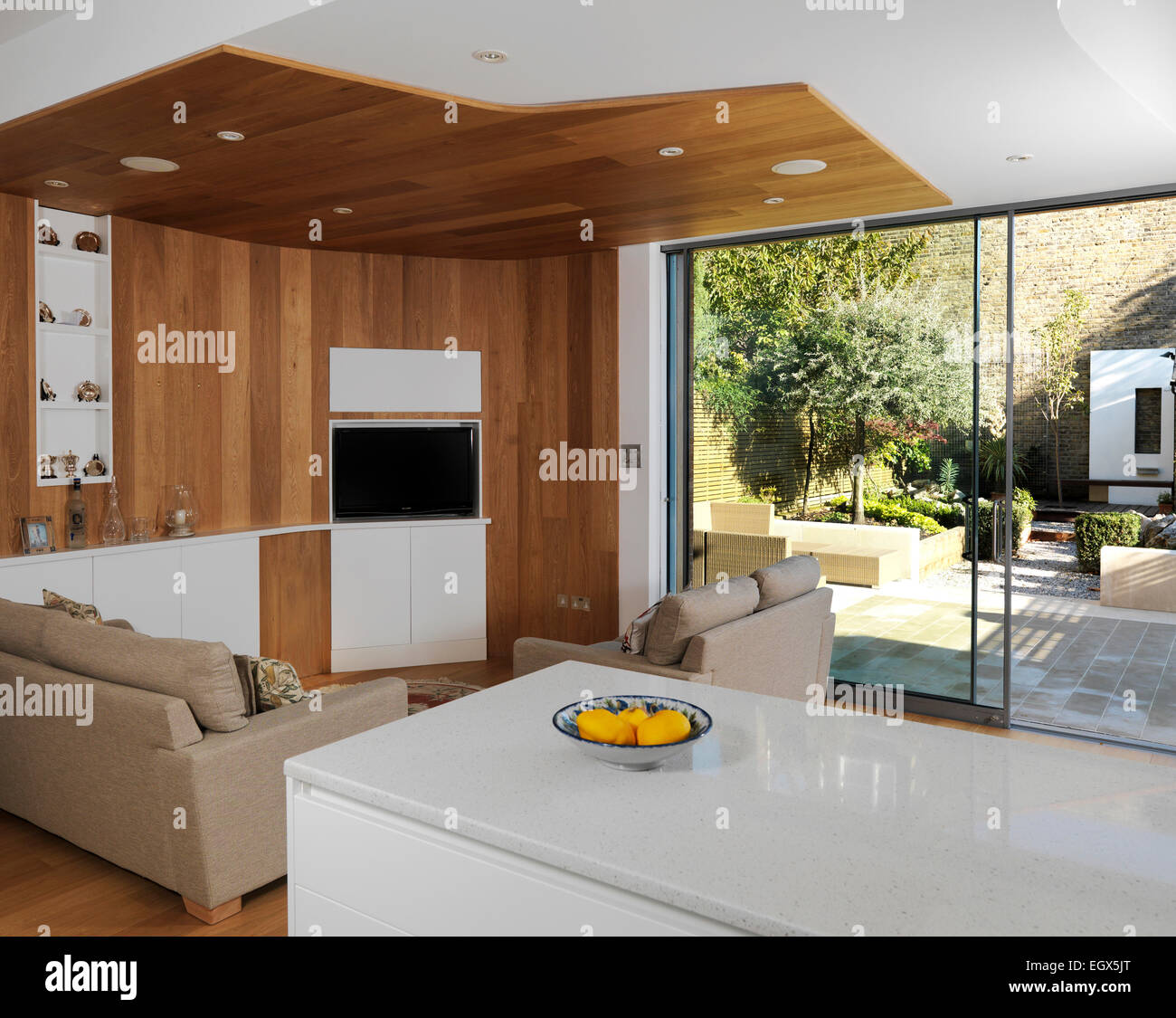 sitting area in open plan kitchen with view to garden, uk home
