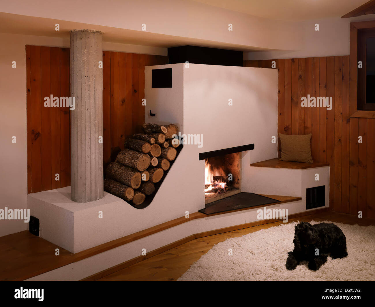Fireplace with log storage in wood panelled living room