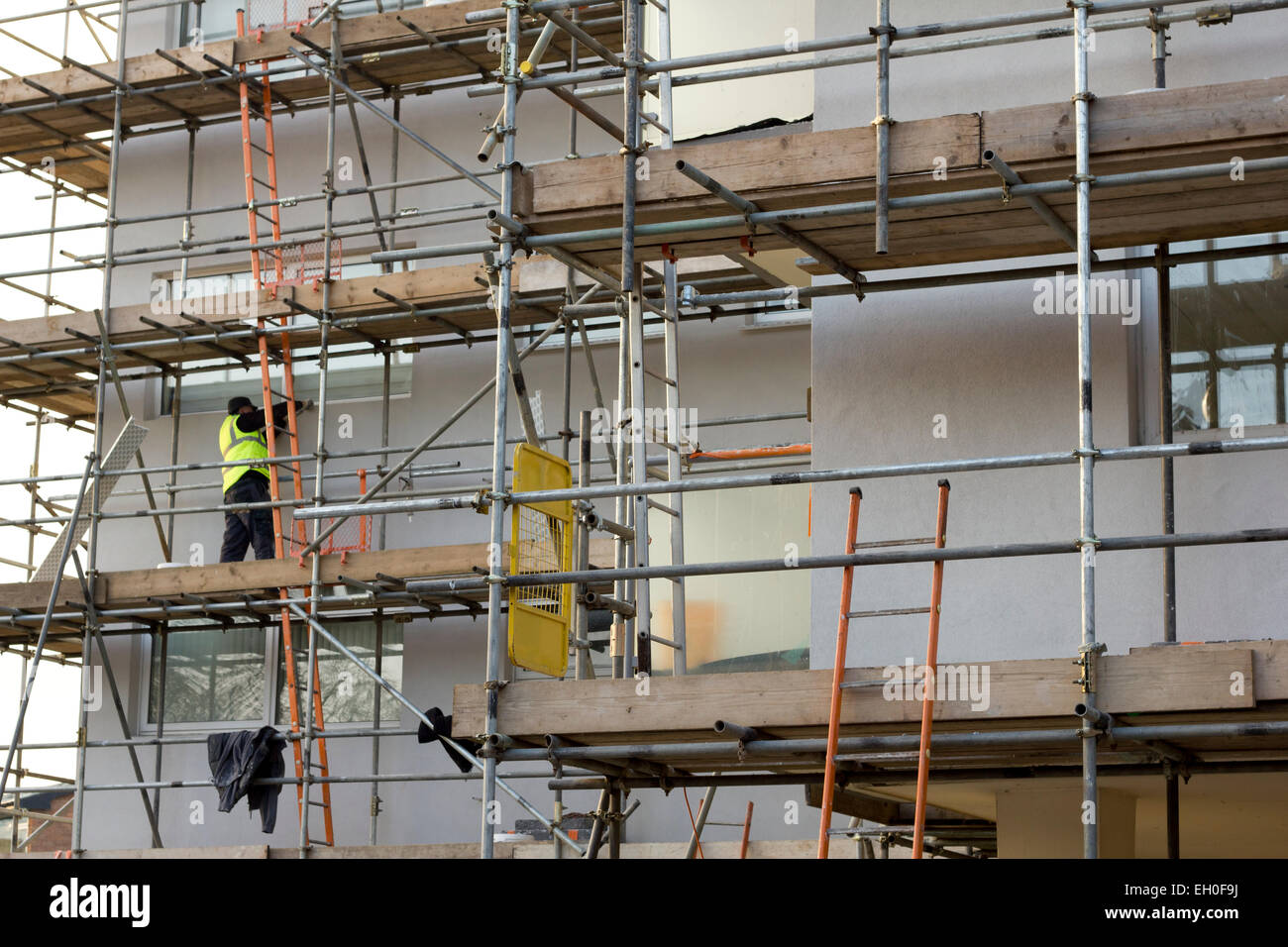 Working On Scaffolding : Man working on scaffolding block of flats building